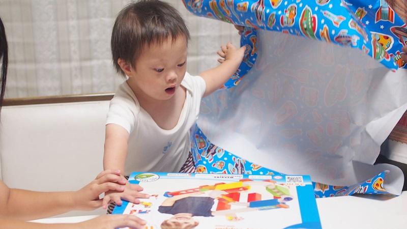 誕生日プレゼントの包装紙を投げ捨てる